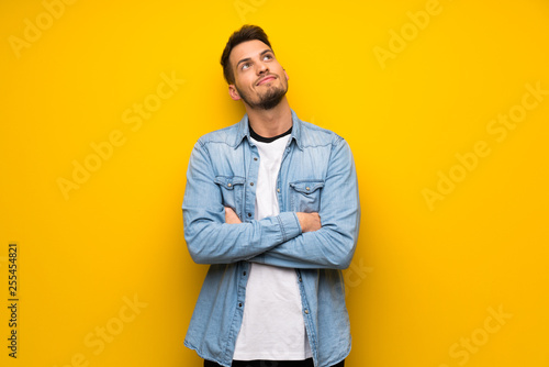 Handsome man over yellow wall looking up while smiling Fototapeta