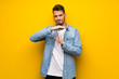 Leinwandbild Motiv Handsome man over yellow wall making time out gesture