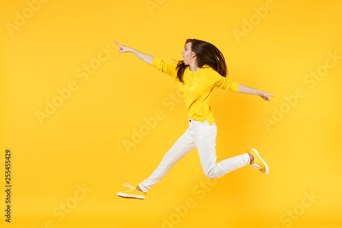 Fotografie, Obraz  Side view of amazed young woman in summer casual clothes jumping, pointing index finger aside isolated on yellow orange wall background