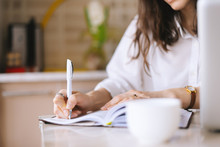 Close Up Of A Woman Writer Hand Writing In A Notebook At Home In The Kitchen