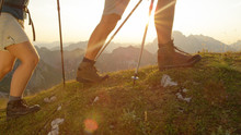 LENS FLARE: Tourist Couple Wearing Hiking Boots Walk Up A Grassy Hill In Alps.