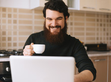 Attractive Young Hispanic Man Enjoying A Cup Of Coffee And Using A Laptop Computer In Kitchen At Home