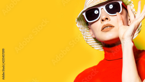 Obraz  Beautiful young woman with sunglasses and hat, retro style on yellow. Summer holiday - fototapety do salonu