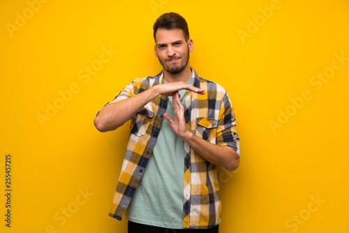 Obraz na plátně  Handsome man over yellow wall making time out gesture