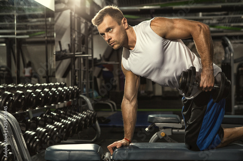 Fototapeta Passion for sports. Handsome young muscular athletic man exercising at the gym weightlifting doing triceps deadlift exercise with dumbbells copyspace motivation lifestyle sportsman athlete muscles  obraz