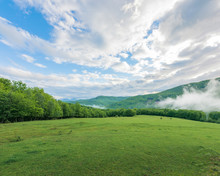 Summer Countryside In Mountains. Fog Rising Behind The Grassy Meadow Among The Forest. Cloudy Morning Sky. Ridge In The Distance.