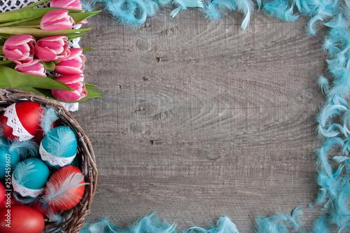 Obraz Wielkanocne tło z różowymi tulipanami, koszykiemi pełnym pisanek i niebieskimi piórami - fototapety do salonu