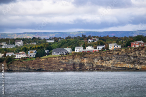 Carta da parati Residential homes on a rocky coast during a cloudy day