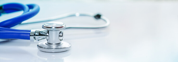 Stethoscope or phonendoscope on a doctor's white desk. Treatment of cold or flu, banner size