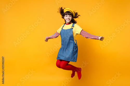 Fotografie, Obraz  Portrait of smiling cute girl teenager in french beret and denim sundress jumping with flowing hair isolated on yellow wall background in studio