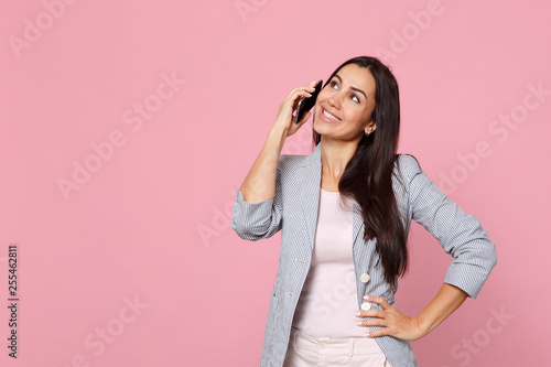 Fotografía  Pretty young woman in striped jacket talking on mobile phone, conducting pleasant conversation isolated on pink pastel wall background