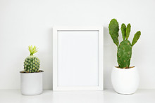 Mock Up White Frame With Cactus Plants On A Shelf Or Desk. White Shelf And Wall. Portrait Frame Orientation.