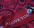White gold diamond ring on top of colored stones. Romantic background ( Valentine's Day)