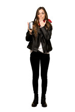 Full-length Shot Of Young Woman With Leather Jacket With Troubled Holding Broken Smartphone On Isolated White Background