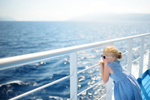 Adorable Young Girl Enjoying Ferry Ride Staring At The Deep Blue Sea. Child Having Fun On Summer Family Vacation In Greece.