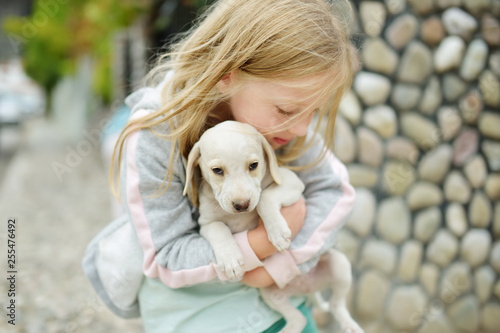 Cute Little Girl Holding Small White Puppy Outdoors Kid Playing With Baby Dog On Summer Day Buy This Stock Photo And Explore Similar Images At Adobe Stock Adobe Stock