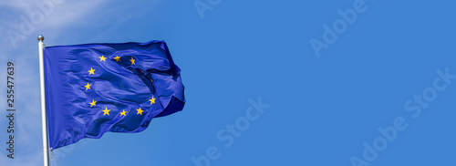 Obraz Flag of the European Union waving in the wind on flagpole against the sky with clouds on sunny day, banner, close-up - fototapety do salonu