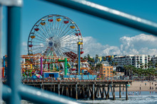 An Amusement Park On Top Of A Pier With A Ferris Wheel, Roller Coaster, And Beach Scene