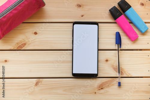 Valokuva  mesa de trabajo con teléfono móvil lapicero, marcadores en escritorio de madera