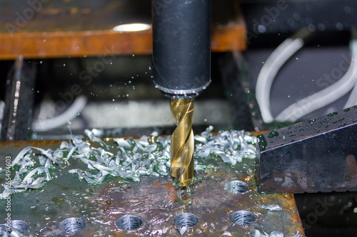 Fotografiet  close up tool of automatic drilling machine make hole at metal with cooling by c