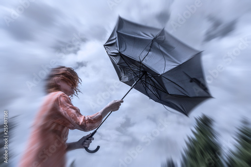 a woman with red hair tries to hold her umbrella in a storm Fototapete