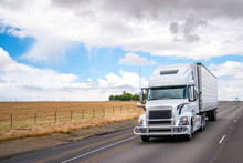 White Big Rig Semi Truck Transporting Food In Refrigerated Semi Trailer Moving On Wide Highway In California