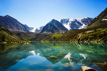 Beautiful mountain lake with turquoise clear water in the Altai Republic Siberia Russia. reflection of mountains with snow-capped peaks in crystal clear water