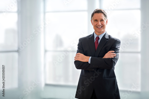 Confident and happy businessman standing with arms crossed, handsome successful smiling portrait, copy space