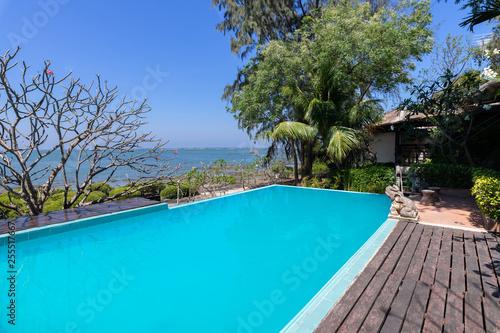 Fototapeta Swimming pool  blue water and tropical garden with sea view background obraz na płótnie