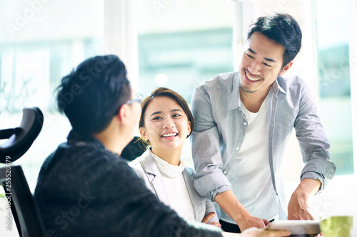 Fotografia  three happy asian teammates discussing business in office