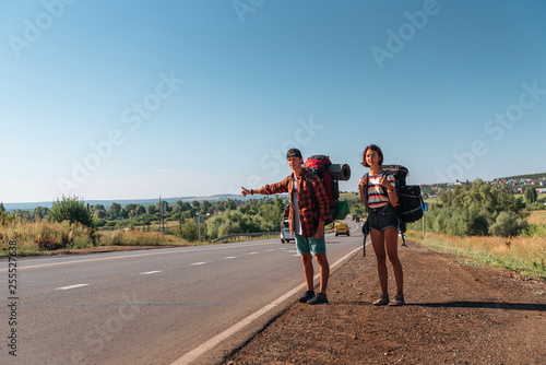 Fotografiet Travel man hitchhiking. Backpacker on road