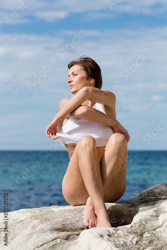 Female person resting on wild rocky seashore Fototapeta