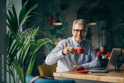 happy senior businessman on coffee break in cafe bar. - 255531056