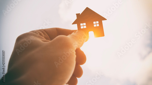 Obraz Man's hand holds wooden flat house against the sun - fototapety do salonu