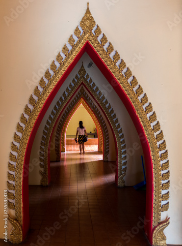 Fotografie, Tablou  Woman walking down arched doorways in Temple