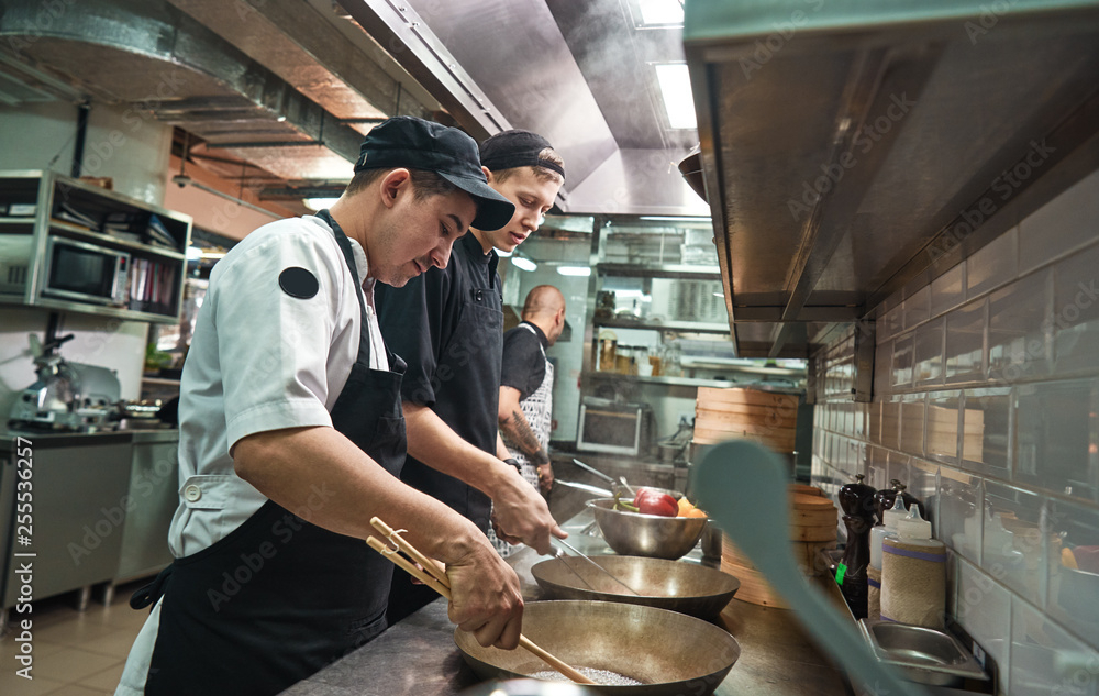 Fototapety, obrazy: New skills. Two chef assistants cooking a new dish in a restaurant kitchen.