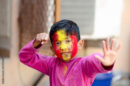 Cute Little Indian boy child with coloured face during holi indian festival look Wallpaper Mural