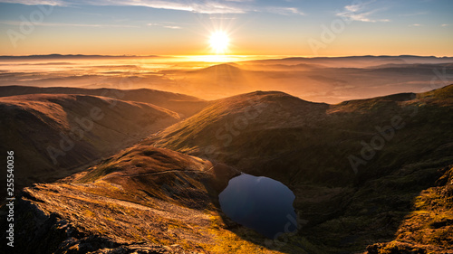 Foto A stunning orange yellow sunrise from Sharp Edge on Blencathra, Lake District, C