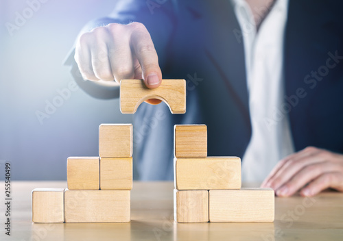 Foto Business man bridging the gap between two towers or parties made from wooden blo