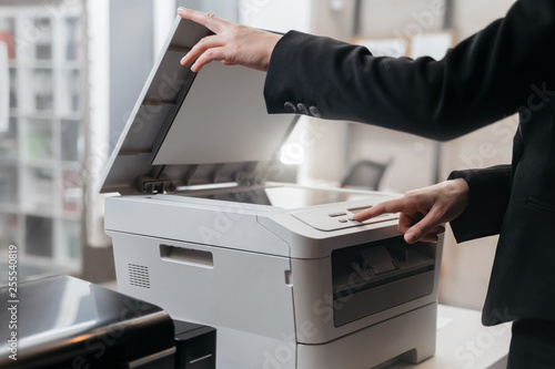 Fotografía  Business woman is using the printer to scanning and printing document