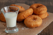 Top View Of Donuts And Glass Of Milk On Paper And Wooden Background