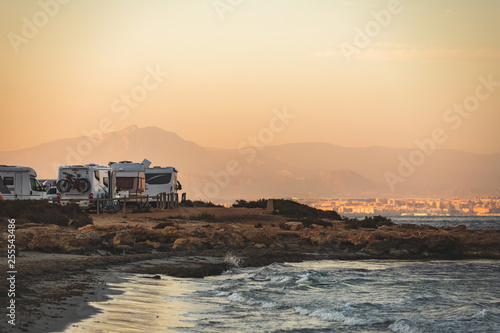 Cuadros en Lienzo Motorhome making wild camp on the beach at a beautiful sunset or sunrise with mountains in the background