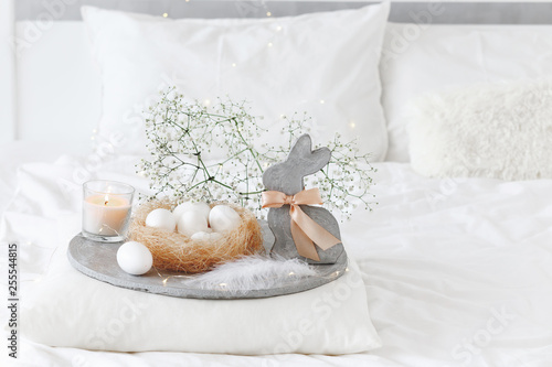 White modern bedroom with Easter decoration. Bed with white bedding set, pillows, concrete tray, nest with white eggs, decorative bunny figure, candle and  gypsophila flowers.