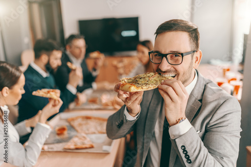 Cuadros en Lienzo Young unshaven businessman in formal wear and eyeglasses eating pizza for lunch