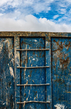 Close-up Of A Old Grungy Weathered Industrial  Dumpster Ladder, Cloudy Sky Background