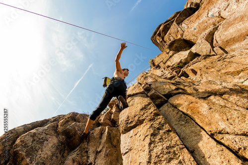 Photo Climber Extreme climbs a rock on a rope with the top insurance, against the blue