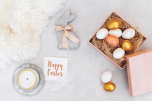 Easter Decoration. Nest With White And Gold Eggs In Pink Box, Decorative Bunny Figure Made Of Concrete, Candle, White Fluffy Plaid And Card With Greeting Happy Easter On Grey Background. Flat Lay.