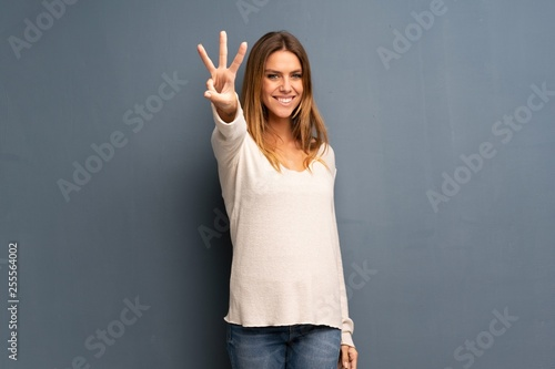 Fotografiet Blonde woman over grey background happy and counting three with fingers
