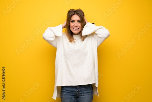Fototapety, obrazy: Blonde woman over yellow wall takes hands on head because has migraine
