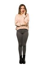 A Full-length Shot Of A Teenager Girl With Pink Sweater Surprised And Shocked While Looking Right Over Isolated White Background
